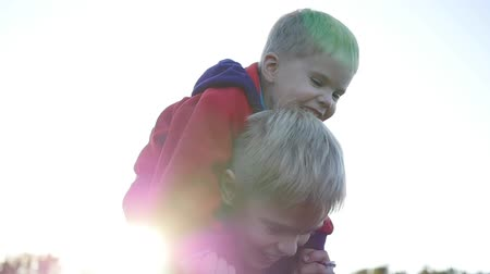 rodzeństwo : Boy hugging his younger brother and holds him on his shoulders. Childrens laughter and joy. Sunset