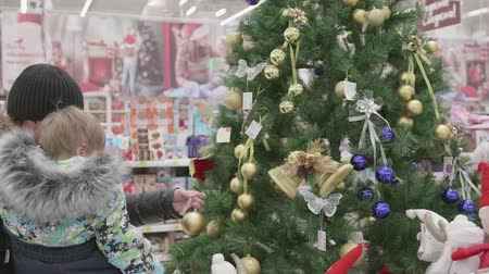 loved : NOVOSIBIRSK,RUSSIA - November 25,2017: Sale of toys and Christmas trees until xmas. People in the supermarket are shopping before the new year. Christmas gifts for loved ones. Stock Footage