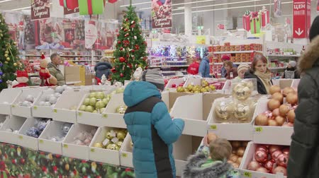 loved : NOVOSIBIRSK,RUSSIA - November 25,2017: Christmas sale of toys and Christmas trees until Christmas. People in the supermarket are shopping before the new year. Christmas gifts for loved ones