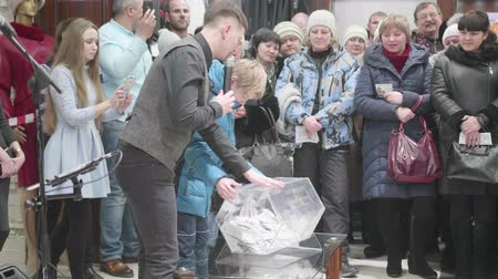 összeg : NOVOSIBIRSK,RUSSIA - February 2 ,2018: The raffle at the Mall. The boy spins the drum with lotteries Stock mozgókép