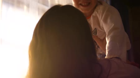 plastelíny : Mother holding little baby in the hands of the house near the window. Sun rays through the window. The laughter and joy of a child.