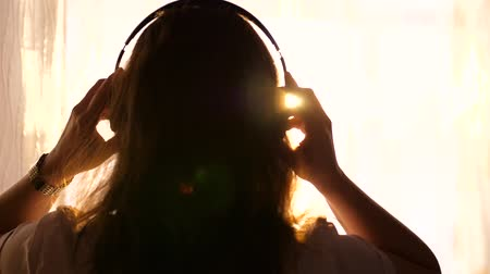 exibindo : A young Girl comes to the window and dresses headphones to listen to music. Blurred background with sunset, woman enjoying the melody in headphones.