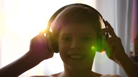 exibindo : A young man stands near the window and puts on headphones to listen to music. Blurred background with sunset, teen enjoying music in headphones.