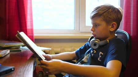 estudioso : Boy sitting at school Desk and does the job. School education. Reading of books. Stock Footage