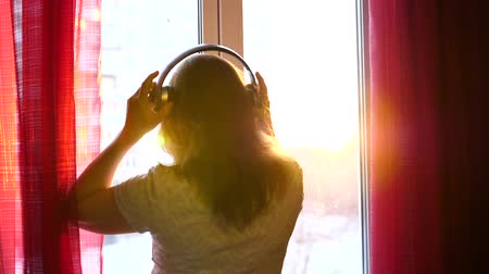 exibindo : A young Girl comes to the window and dresses headphones to listen to music. Blurred background with sunset, woman enjoying the melody in headphones. The suns rays pass through the glass Stock Footage