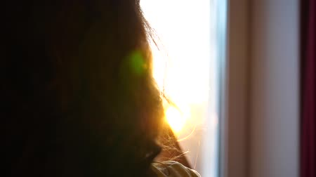 exibindo : Close up. A young Girl comes to the window and dresses headphones to listen to music. Blurred background with sunset, woman enjoying the melody in headphones. The suns rays pass through the glass Stock Footage