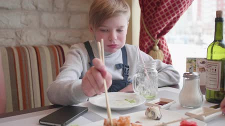 oneperson : A young man sits in a cafe and eats sushi with sticks. A dish of traditional Japanese cuisine, cooked rice with acetic seasoning and assorted seafood