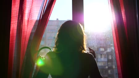 exibindo : A young girl comes to the window and dresses headphones to listen to music. The girl enjoys music with headphones, dancing. The suns rays pass through the glass Stock Footage