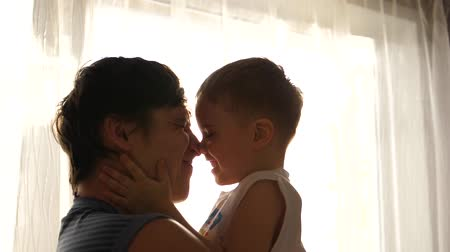 plastelíny : Young father holding his small child near a window. Sun rays through the window. Laughter and joy of the child. Dostupné videozáznamy