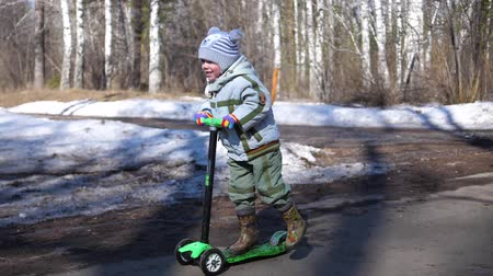 midair : The child rides a scooter in the Park in early spring. Melting snow, snow and puddles on asphalt. Outdoor sports Stock Footage