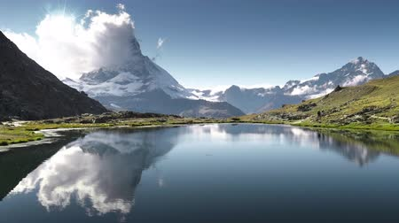 vakáció : Reflection of Matterhorn in lake Riffelsee, Zermatt, Switzerland Stock mozgókép