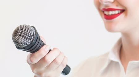 novinář : Close up portrait of  beautiful woman tv reporter with red lips, who is smiling while holding the microphone and speaking with someone and listening to them very attentively, isolated on a grey background Dostupné videozáznamy