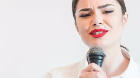 śpiew : Waist up portrait of beautiful woman tv reporter with pretty smile and red lips, who is singing very emotionally and looking at the camera while holding the microphone, isolated on a grey background and there is copy place in the left side Wideo