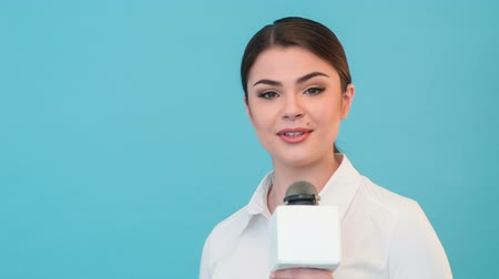 novinář : Half length portrait of woman reporter with long brown hair, who is interviewing and is smiling and looking at the camera holding the microphone. Sometimes she is making gestures with her right hand, isolated on a blue background and there is copy place i
