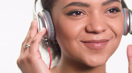 зубастая улыбка : closeup portrait of an African American girl who selects your favorite music on an mp3 player with headphones. smiling and dancing looking at the camera