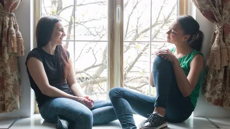 slide the camera from left to right, two girls sitting on the window sill and talk. Dressed in jeans and t-shirts