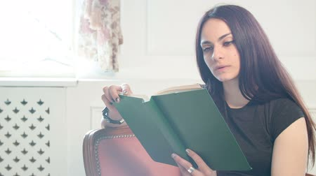 girl reading a book in hardcover sitting on the couch. from time to time she glances out the window and dreams Stok Video