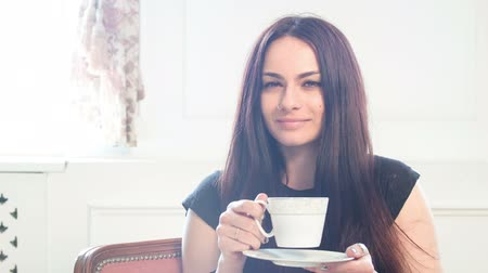 girl drinking coffee and enjoying. looking at the camera and smiles. window on the background Stok Video