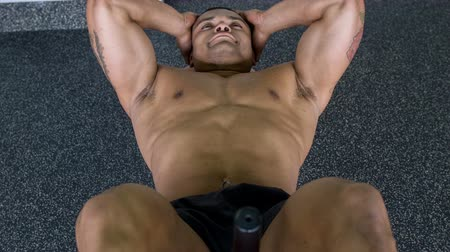 feszült : Handsome sportsman is doing sit-ups in gym. He is very strained