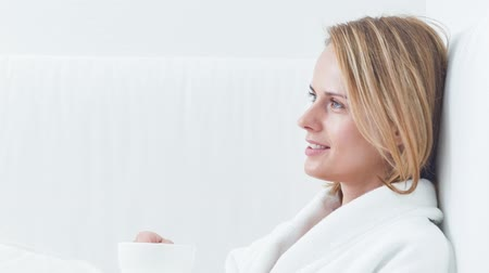 Cheerful young woman enjoying hot beverage at spa