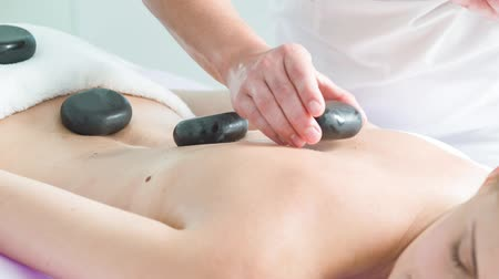 estância termal : Skillful beautician massaging female body by stones