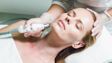 Professional beautician massaging female face by device