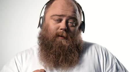Calm fat man enjoying song from headphones