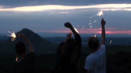 разнообразие : Friends at sunset in the mountains rejoice and waving sparklers.