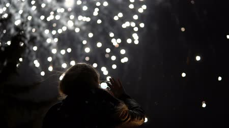 bohyně : The girl takes pictures of fireworks on a mobile phone. Silhouette on the background of the sky illuminated by lights.