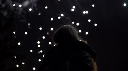 final destination : The girl takes pictures of fireworks on a mobile phone. Silhouette on the background of the sky illuminated by lights.