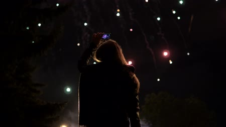 fişekçilik : The girl takes pictures of fireworks on a mobile phone. Silhouette on the background of the sky illuminated by lights.