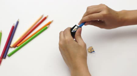 ołówek : Woman hand using sharpener with color pencil on white desk Wideo