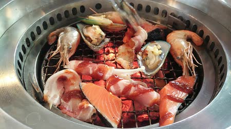 бекон : Korean barbecue stoves with chacoal, put raw shrimp, mussel, fish, bacon inside Стоковые видеозаписи