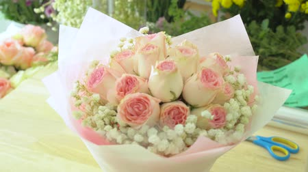 flower shops : Flower shop, arranging flower bouquet, hand of florist spraying water on pink rose bouquet