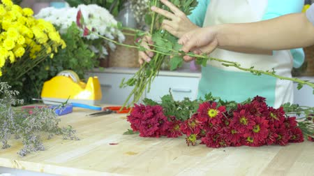 bouquets : Flower shop, various flowers, florist preparing flower, cutting red mums stem , arranging flower bouquet