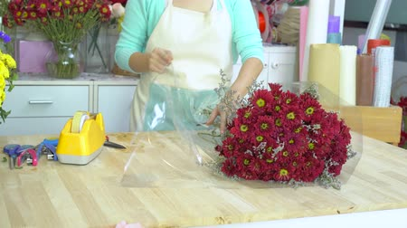 kwiaciarnia : Flower shop, florist arranging red mums bouquet, wrapping cellophane around red mums bouquet