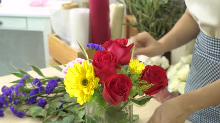 flower shops : Florist woman cutting flowers and arranging beautiful flowers in a flower glass vase