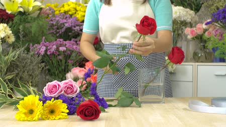 flower shops : Dolly shot of florist woman cutting and arranging flowers in a flower glass vase Stock Footage