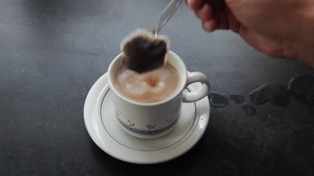 teabag : Cup with a teabag being stirred.