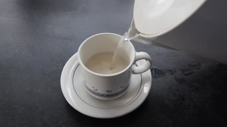 koflík na čaj : Teacup being filled with boiling water.