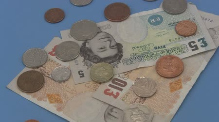 notes : Close up of sterling UK cash and coins rotating a blue background.