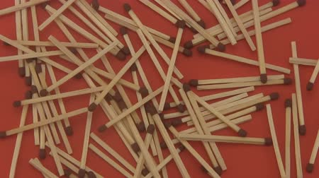 rotační : Close up of a pile of wooden matches rotating on a red  background.