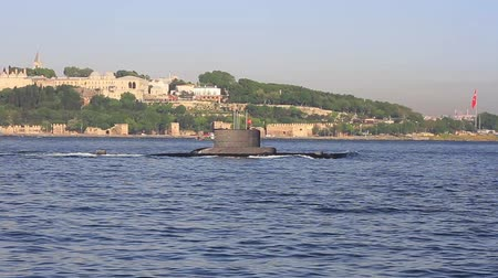 periscope : Submarine on the sea surface. Turkish navy submarine passes through Bosphorus as the historic Topkapi Palace is seen in the background.  Stock Footage