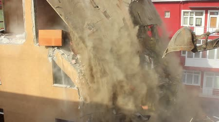 yıkım : Bulldozers turn old homes into rubble and dust fills the air. Tearing down old building on a construction site. Concrete dust released by a building demolition is a major source of dangerous air pollution. Some substances in concrete can cause health conc