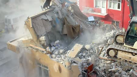 destroyed building : Crawler dozer turning homes into rubble Tearing down old building on a construction site. Concrete dust released by a building demolition is a major source of dangerous air pollution. Some substances in concrete can cause health concerns due to toxicity.