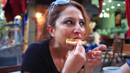 İtalyan : Portrait of young woman eating a slice of pizza