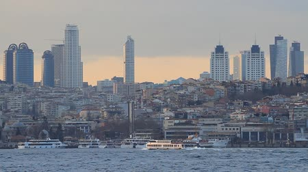 skyscraper : Istanbul city skyline at sunset, showing the buildings rising above Besiktas viewed from Uskudar coast Stock Footage