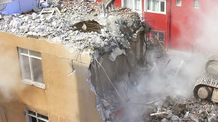 destroyed building : Crawler dozer turning homes into rubble and dust fills the air. Some substances in concrete can cause health concerns due to toxicity. Demolition of building with concrete floors and pillars on construction site