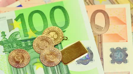 lira : Closeup of gold coins over European banknotes. Perfect for any financial, commerce, treasury or banking video needs. Gold coins and a goldbar falling on Euro banknotes Stok Video