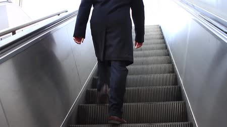 escada : Low angle view looking to exit of modern escalator at Taksim Subway Station. Man walking up stairs from subway station Stock Footage